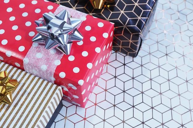 Caixas de presente em ouro preto e vermelho em ervilhas brancas em ângulo em papel branco