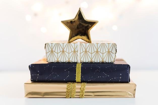 Caixas de presente em papéis do docinho com estrela de ornamento perto de luzes de fadas