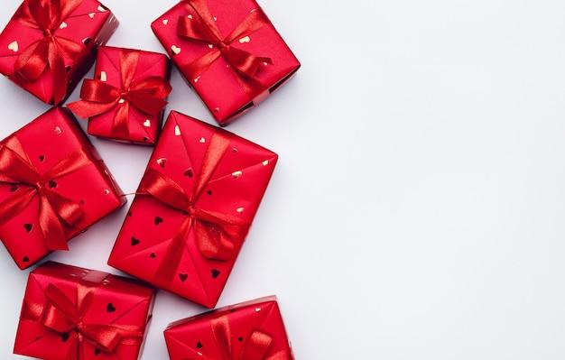 Caixas de presente em papel vermelho amarrado com fitas de cetim com laços