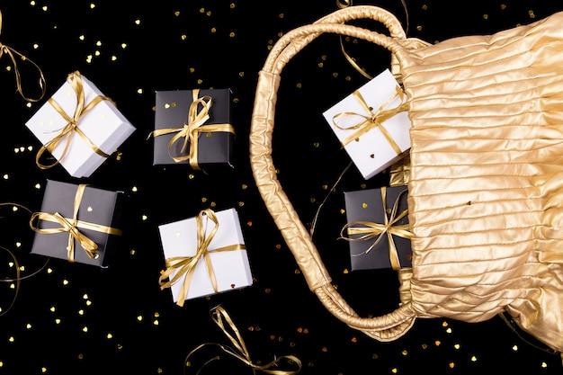 Caixas de presente em preto e branco com fita dourada saem da bolsa dourada na superfície de brilho,