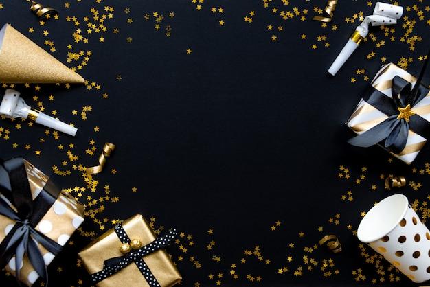 Caixas de presente em vários papéis de embrulho padrão ouro sobre estrela em forma de lantejoulas douradas sobre um fundo preto.