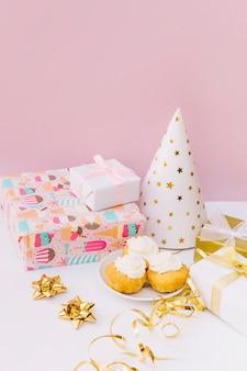 Caixas de presente embrulhadas; arco; flâmula; chapéu de festa e cupcakes na mesa contra fundo rosa