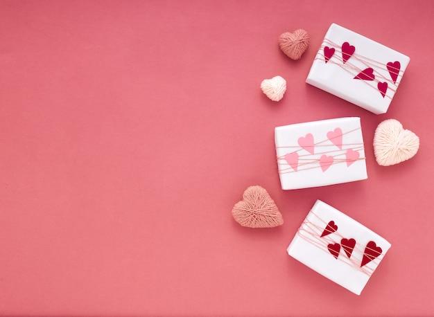 Caixas de presente embrulhadas brancas em fundo rosa com trança e corações com espaço de cópia