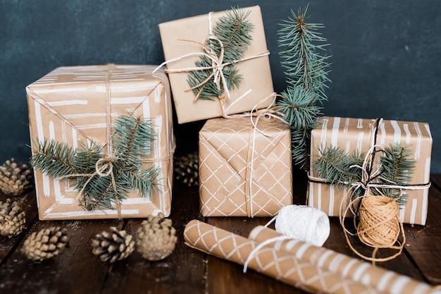 Caixas de presente embrulhadas com coníferas no topo, papel enrolado, fios para encadernar e pinhas perto de fazer composição de natal