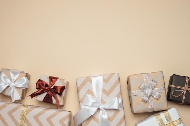 Caixas de presente embrulhadas com fita branca, prata e dourada e laço na mesa bege.