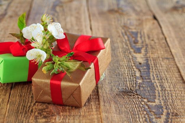 Caixas de presente embrulhadas com fitas vermelhas decoradas com flores de jasmim em placas de madeira.
