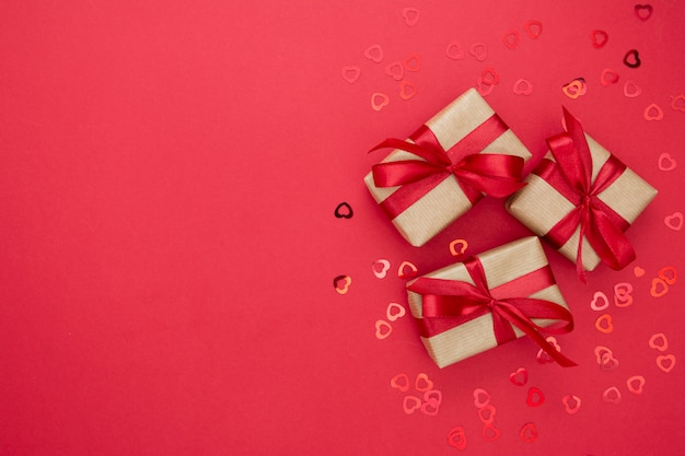 Caixas de presente embrulhadas com papel kraft e laço vermelho, isolado no fundo vermelho. resumo plano leigos.
