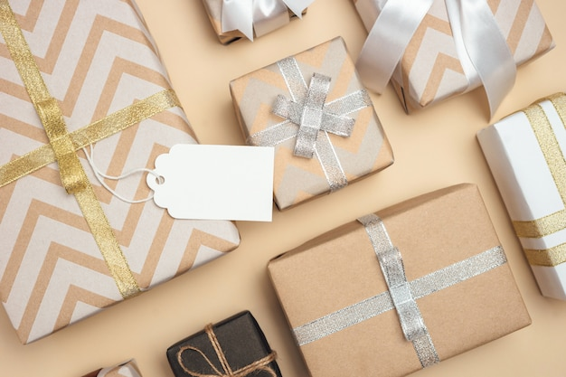 Caixas de presente embrulhadas em papel kraft com fita branca, prata e dourada e laço na mesa bege pastel. etiqueta de presente em branco. conceito presente de férias. vista do topo.