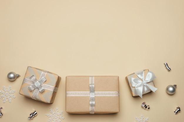 Caixas de presente embrulhadas em papel kraft com fita prata e laço bege.