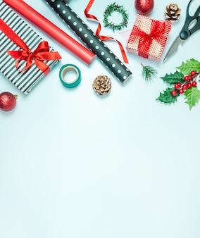Caixas de presente embrulhadas em papel listrado preto e branco e vermelho com materiais de embalagem sobre um fundo azul. preparação de presentes de natal.