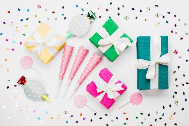 Caixas de presente embrulhadas; soprador de chifre de festa; prop cercado com confete no fundo branco
