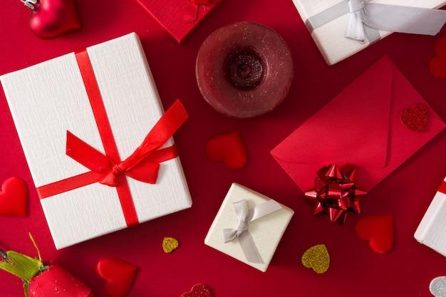 Caixas de presente, envelope de papel vermelho e corações vermelhos em fundo vermelho