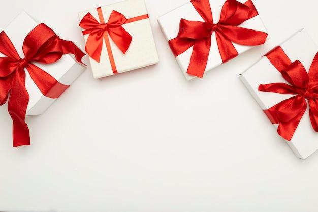 Caixas de presente festivas com laços vermelhos