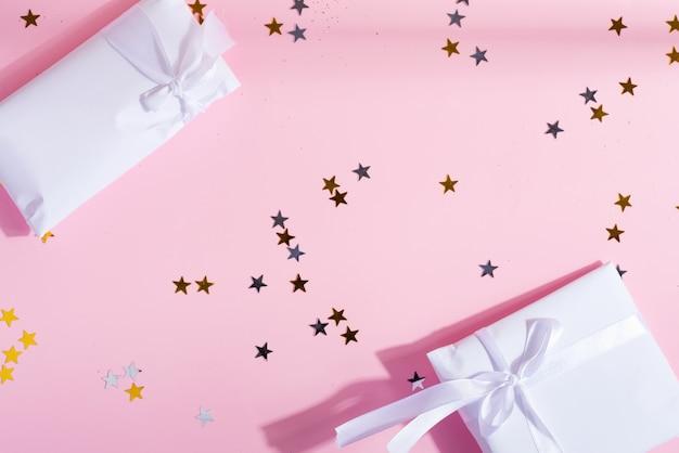 Caixas de presente festivas e decoração de confete estrela brilhante em um rosa pastel. postura plana.