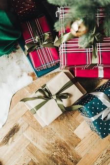 Caixas de presente festivas feitas à mão, embrulhadas em papel nas cores vermelho, azul e bege embaixo da árvore de natal, no chão de madeira