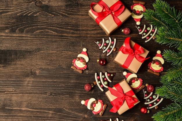 Caixas de presente festivo natal em fundo de madeira. bombons de chocolate em forma de uma árvore de natal e papai noel.