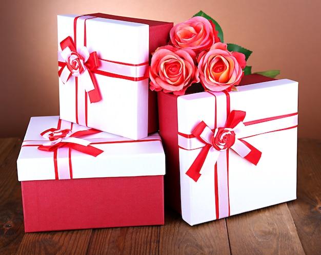 Caixas de presente lindas com flores na mesa em fundo marrom