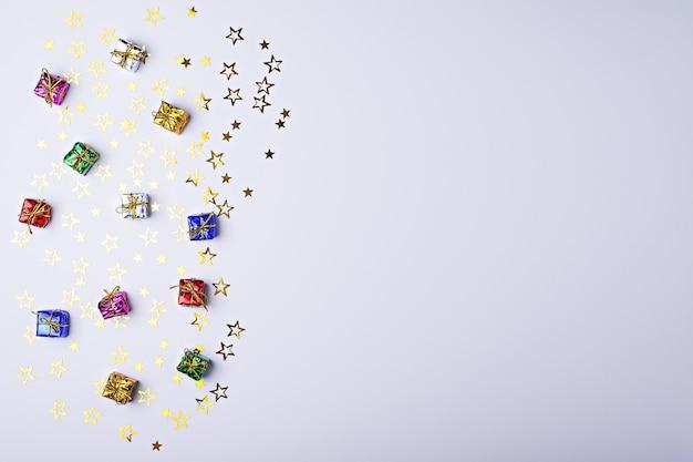Caixas de presente multicoloridas com estrelas brilhantes em fundo branco com espaço de cópia