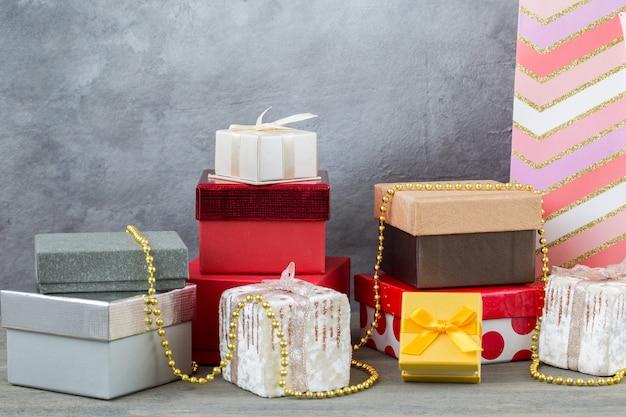 Caixas de presente na mesa em diferentes cores e tamanhos, saco de papel de embrulho, contas de ouro