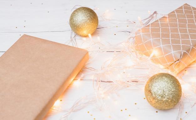Caixas de presente no envoltório e bolas de natal perto de luzes de fadas iluminadas