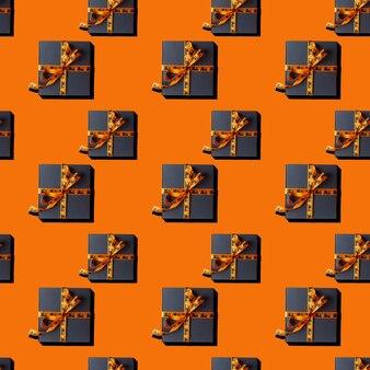 Caixas de presente padrão sem emenda amarradas com fita com decoração de halloween em fundo laranja