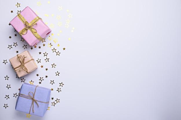 Caixas de presente pastel com estrelas brilhantes em fundo branco com espaço de cópia