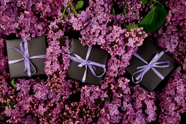 Caixas de presente pequenas pretas embrulhadas fita roxa com lilás natural.