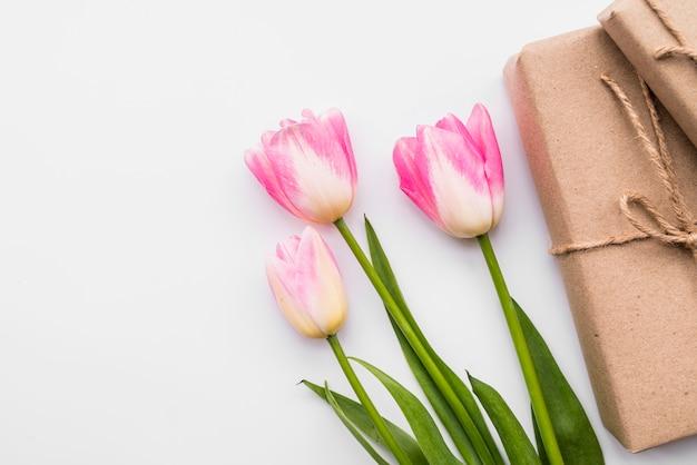 Caixas de presente perto de bando de flores cor de rosa