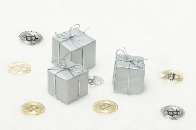 Caixas de presente prateado e moedas de bitcoins em um fundo branco