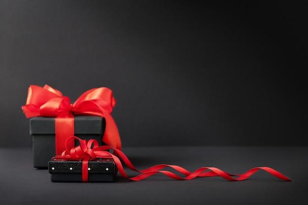 Caixas de presente pretas com fita vermelha em fundo preto