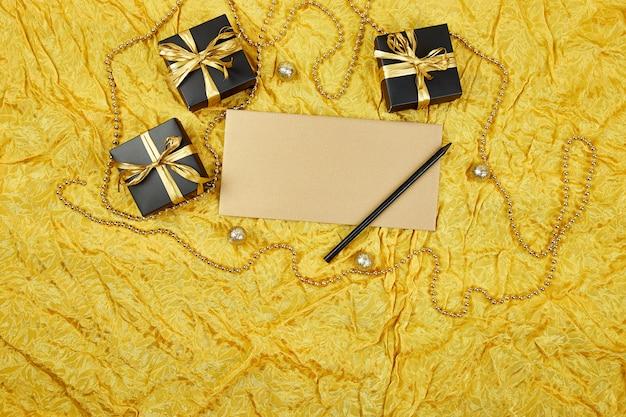 Caixas de presente preto com fita ouro e folha de papel em branco
