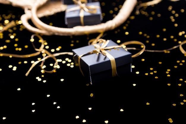 Caixas de presente preto com fita ouro saem da bolsa dourada sobre fundo de brilho. fechar-se.