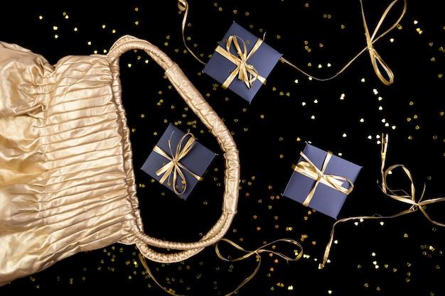 Caixas de presente preto com fita ouro saem da bolsa dourada sobre fundo de brilho. postura plana.