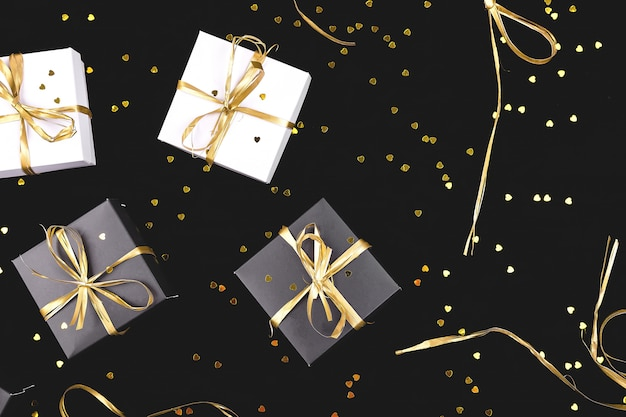 Caixas de presente preto e branco com fita de ouro. postura plana. copie o espaço