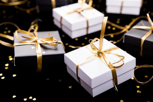 Caixas de presente preto e branco com fita de ouro sobre fundo de brilho