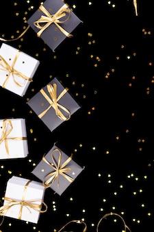 Caixas de presente preto e branco com fita dourada sobre fundo brilhante