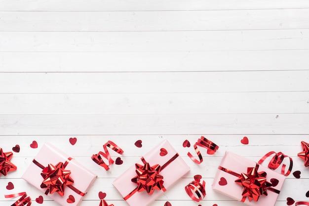 Caixas de presente rosa com fitas vermelhas e arcos, corações de confetes em um fundo branco. copie o espaço lay plana. cartão para festa de aniversário, dia dos namorados casamento.