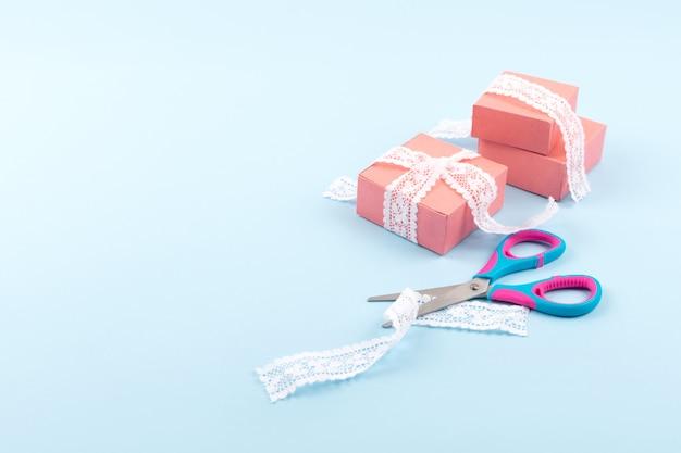 Caixas de presente rosa com laço e tesoura