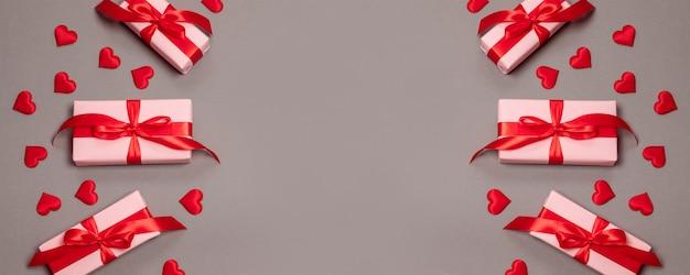 Caixas de presente rosa com laço vermelho no fundo rosa com forma de amor vermelho. banner de férias para o site. dia dos namorados.