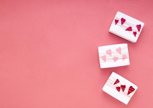 Caixas de presente simples e clássicas com embrulho branco em fundo rosa com tranças e corações de papel com espaço de cópia