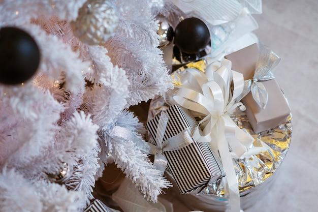 Caixas de presente variadas sob a árvore na casa de celebração de natal de véspera de feriado decorada com ...