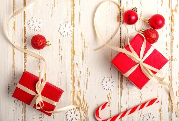 Caixas de presente vermelha, brinquedo de natal, ramos de abeto, doces de natal, sobre o fundo branco de madeira.