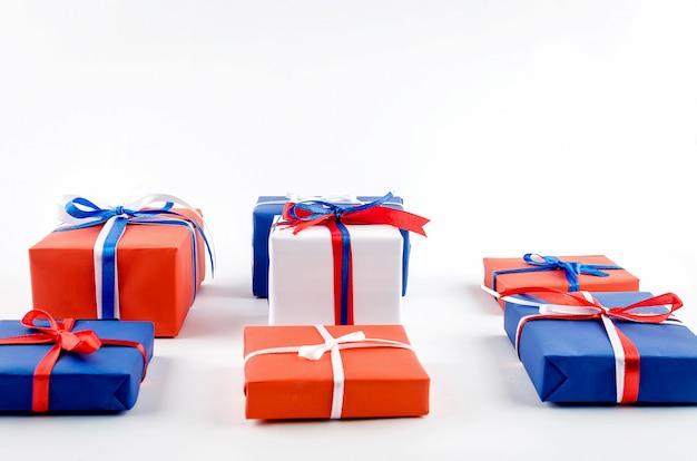 Caixas de presente vermelhas, azuis e brancas com fitas em um fundo branco