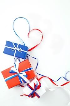 Caixas de presente vermelhas, azuis e brancas sobre fundo branco, conceito do dia da independência, aniversário, festa