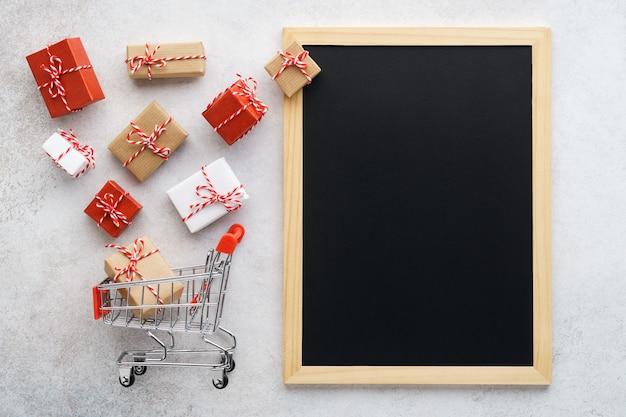 Caixas de presente voando para fora de um carrinho de compras e um quadro-negro vazio