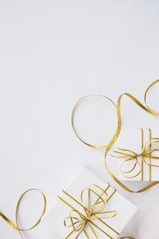 Caixas de presentes com arcos perto de fita