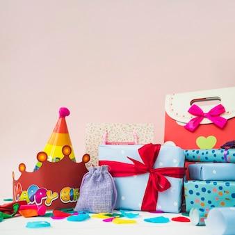 Caixas de presentes com coroas; balões e sacolas de compras contra fundo rosa