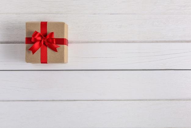 Caixas de presentes com fitas festivas na parede de madeira branca