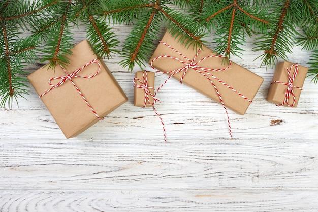 Caixas de presentes com ramos de abeto na vista superior do plano de fundo de madeira