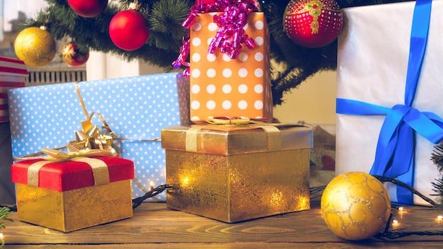 Caixas de presentes de natal em papel de embrulho e enfeites coloridos na sala